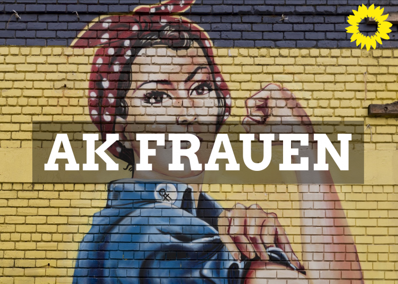 auf einer Mauer zeigt sich das Bild einer Frau mit roten-weiß gepunkteten Kopftuch, welche den:die Betrachtende stark und entschlossen anblickt und ihre Armmuskeln zeigt. Feminismus AK Frauen