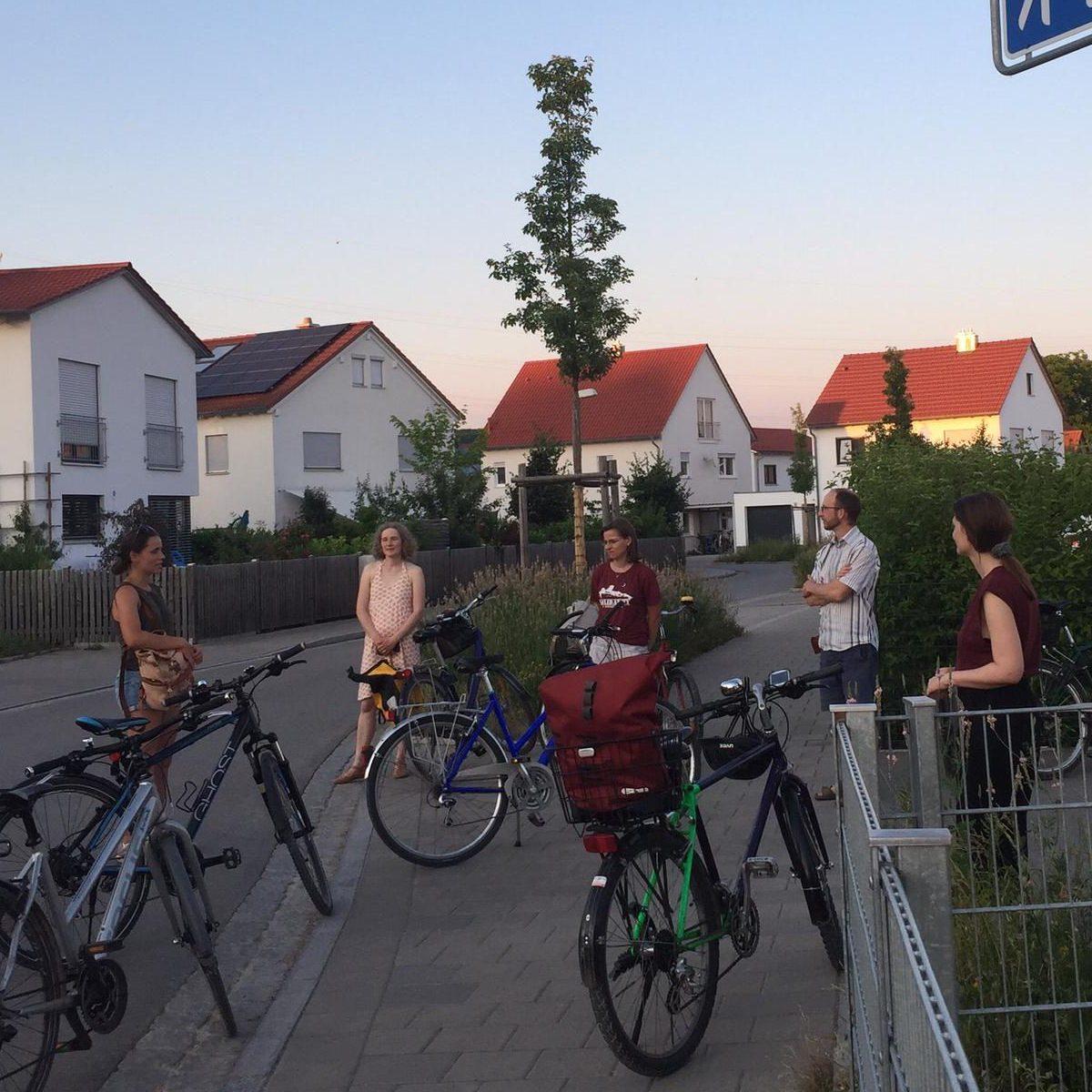 Menschen mit Fahrrädern an einer Kreuzung in einem Neubaugebiet. Daneben ein Straßenschild mit dem Namen Gabriele-Münter-Straße